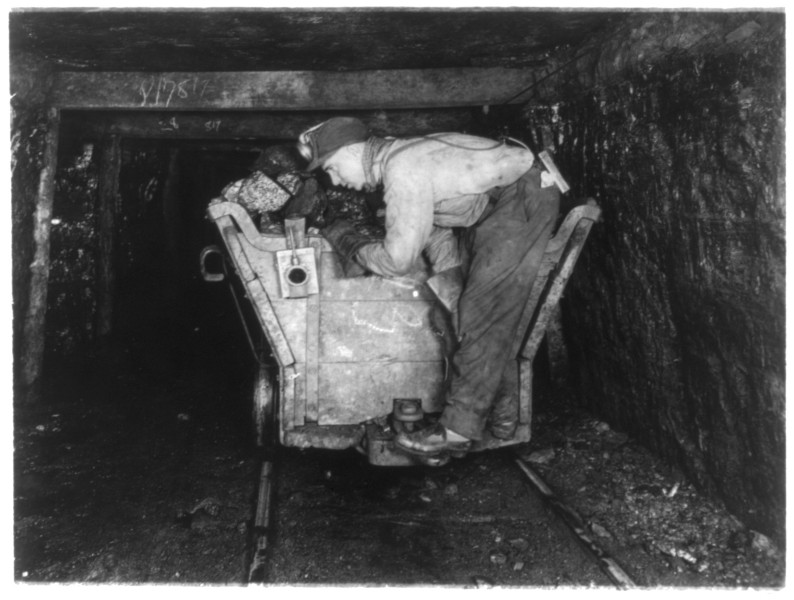 Mineur campé sur un wagonnet chargé de morceaux de charbon au début du 20e siècle