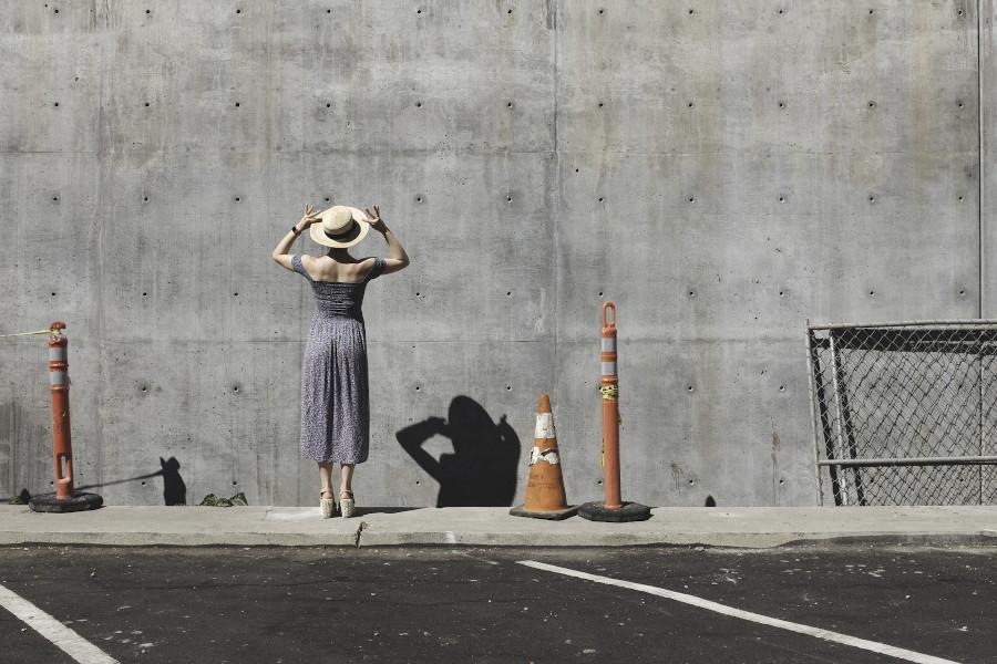 Une femme devant un mur de béton