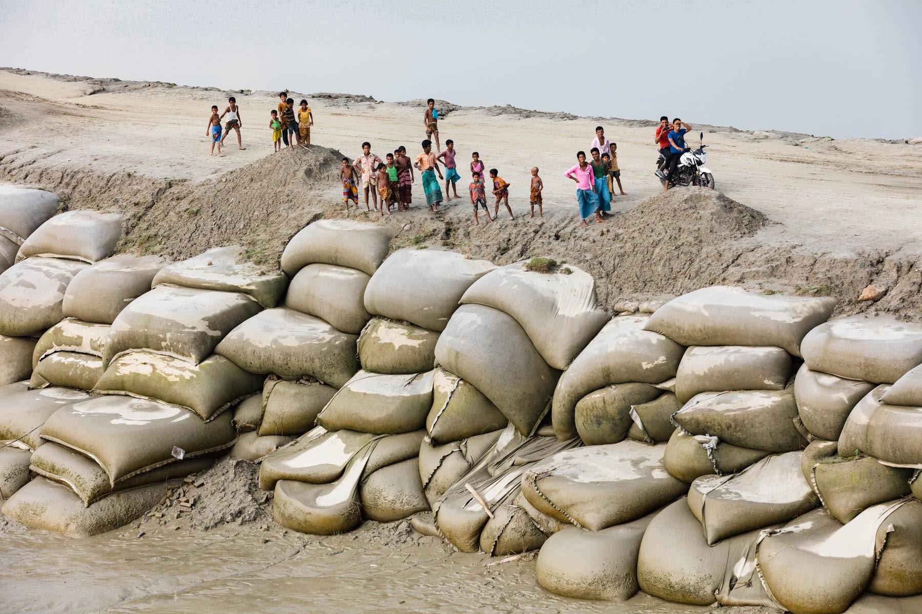 Barrage édifié en sacs de sable sur le delta du Gange au Bangladesh pour contrer la montée des eaux (Chittagong District). Si l'on ne parvient pas à réduire nos émissions de gaz à effet de serre, de nombreux territoires seront recouverts par les océans. © Yann Arthus-Bertrand